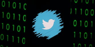 A darkened phone showing the logo of Twitter with a binary 0 and 1 background.