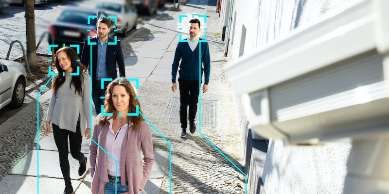 People walking on a sidewalk with a camera using facial recognition to scan them.