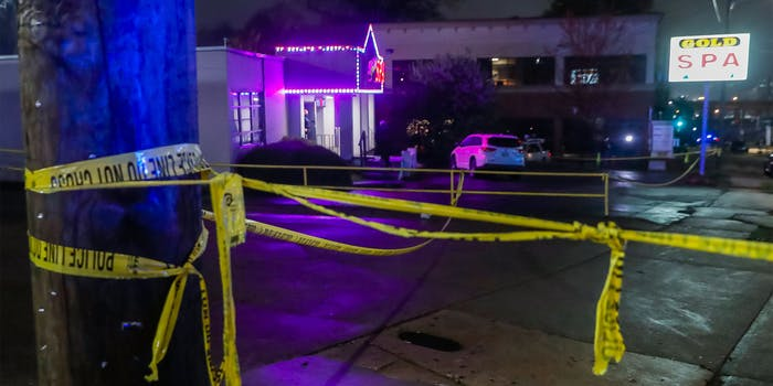 "Yellow police tape surrounds the scene of spa shootings, sign says ""Gold spa"""