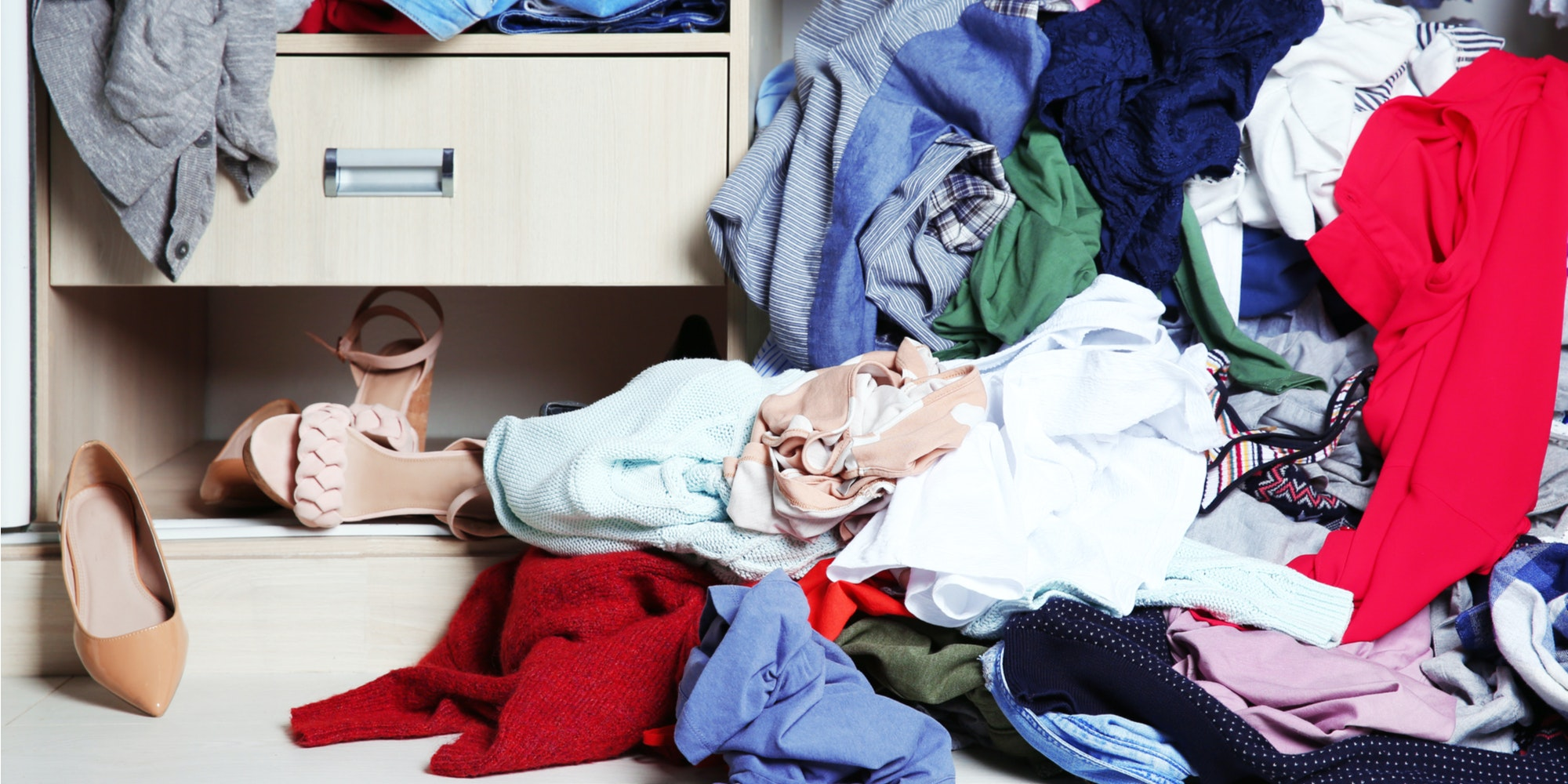 Pile of clothes and shows on floor of closet