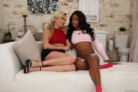 Adira Allure and Lacey London snuggle up on the couch.
