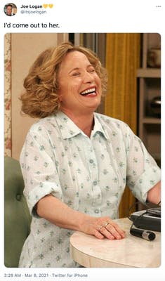 """""""I'd come out to her."""" Kitty, an older white woman in a floral dress throws her head back laughing"""