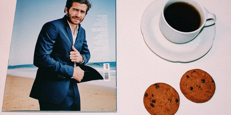A magazine and cup of coffee with cookies.