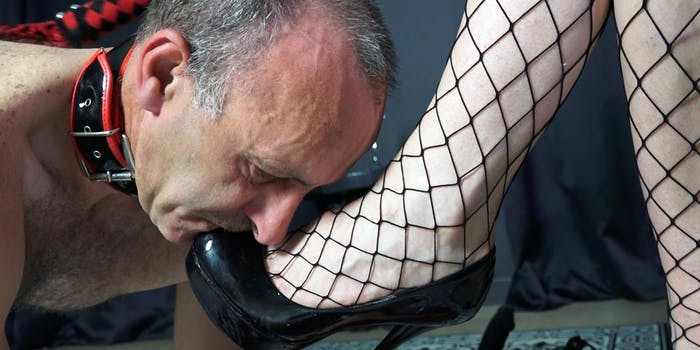 Male performer kisses dominatrix's feet.