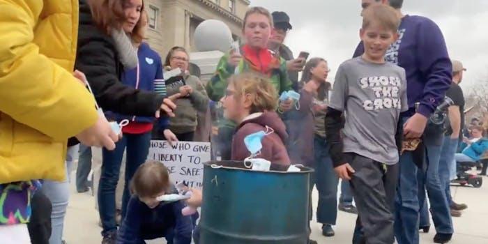 Kids burning face masks at a protest