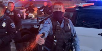 Minneapolis police officer J Spee sprays chemical agent toward camera while officers struggle in the background