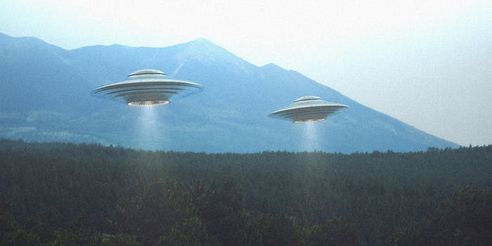 Two UFO ships above forest setting.