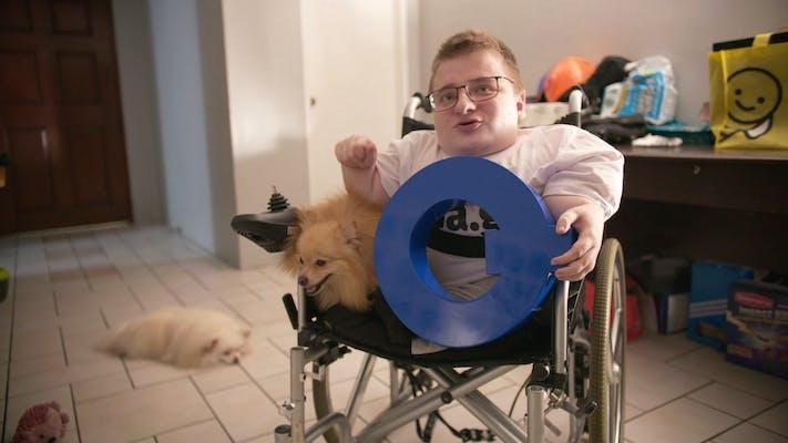 man in wheelchair holding letter q