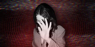 A woman blocks her face from being photographed over a red background.