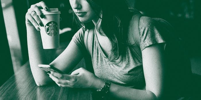 A woman drinking coffee on her phone.