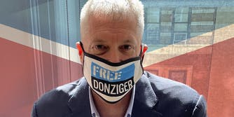 """Steven Donziger wearing """"Free Donziger"""" facemask over Chevron logo background"""
