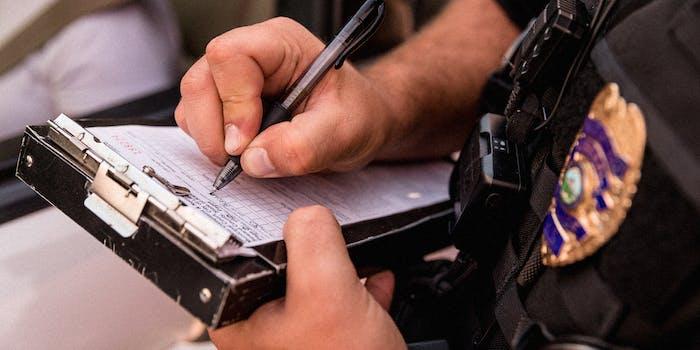 An officer's hands writing a ticket.