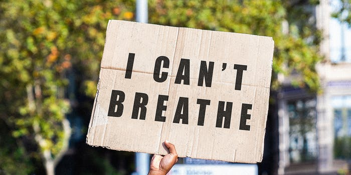 A hand holding a sign that read 'I Can't Breathe.'