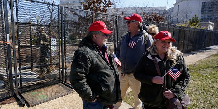 People in Trump caps stand outside fence in Washington DC holding small US flags