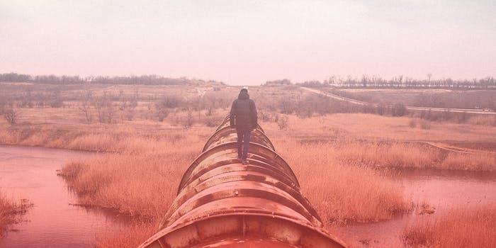 A man walks on an industrial pipeline.