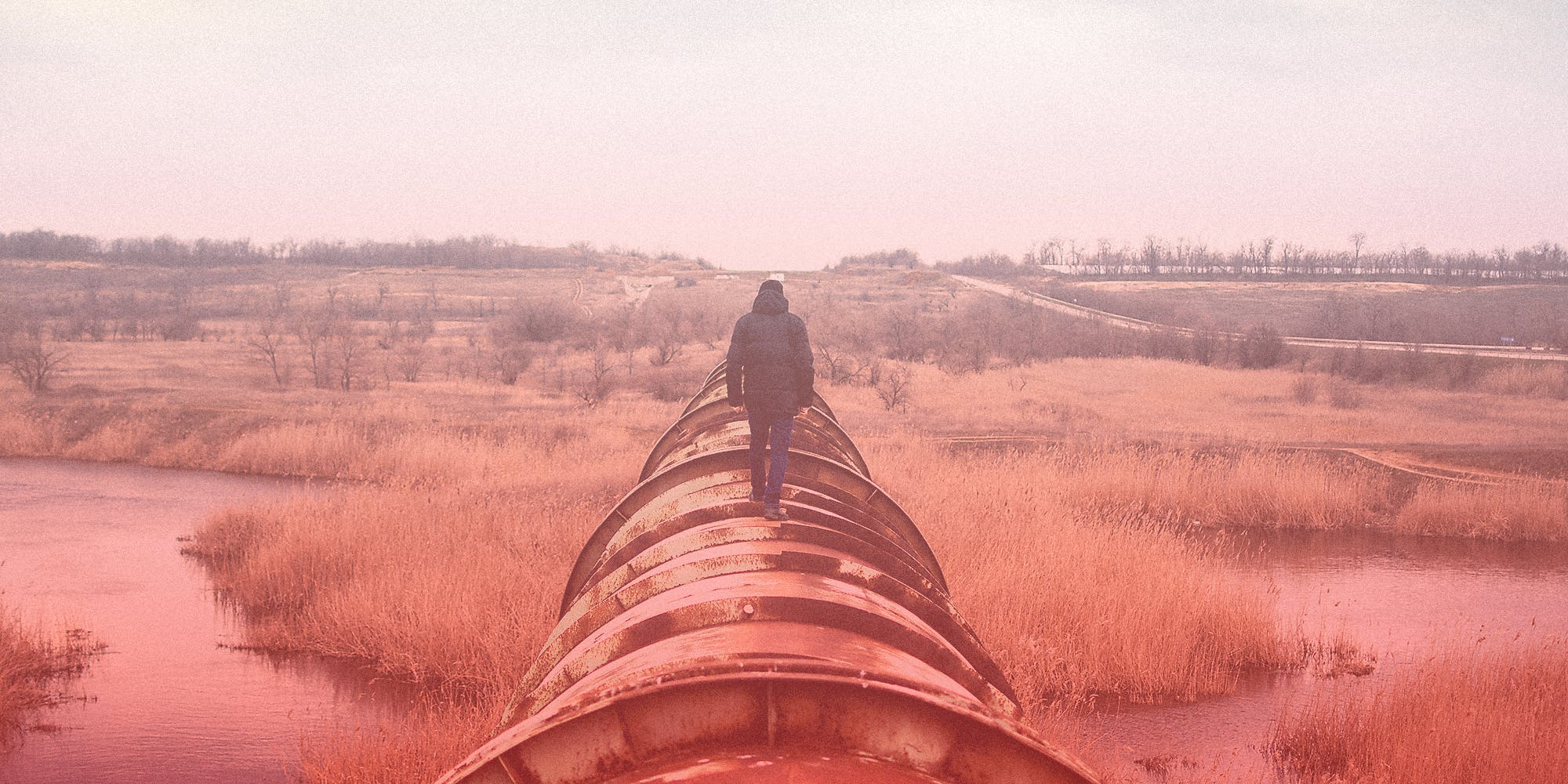 A man walks on an industrial pipeline.