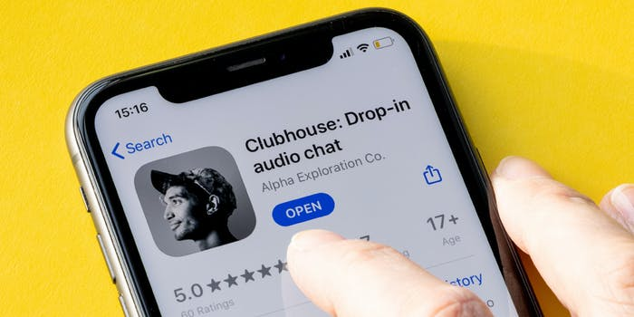 A person's finger touching the Clubhouse app on a phone.