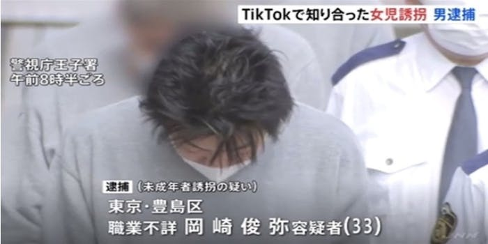 Man in Tokyo wearing a grey sweatshirt and white mask with his hands behind his back after being arrested for kidnapping girl he met on TikTok