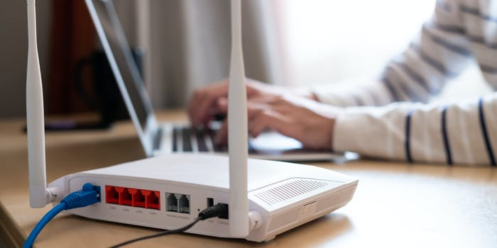 A person typing on a laptop that is connected to broadband internet through a router.