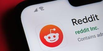 Reddit app seen on the corner of mobile phone.