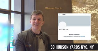 james o keefe in front of cnn building with screen shot of twitter supsension