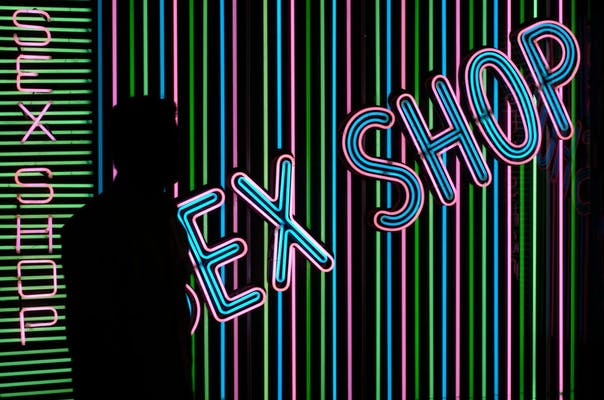 A silhouette stands next to a 'sex shop' sign
