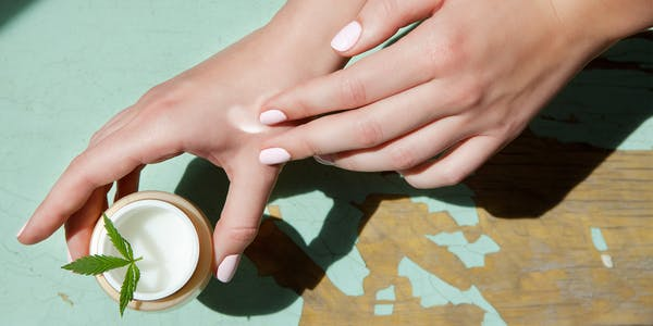 woman applies a cannabis salve CBD topical cream to her hand.