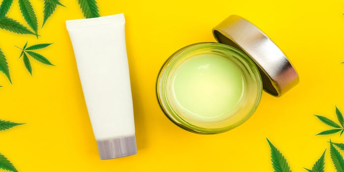 CBD lotion and salve on yellow background.