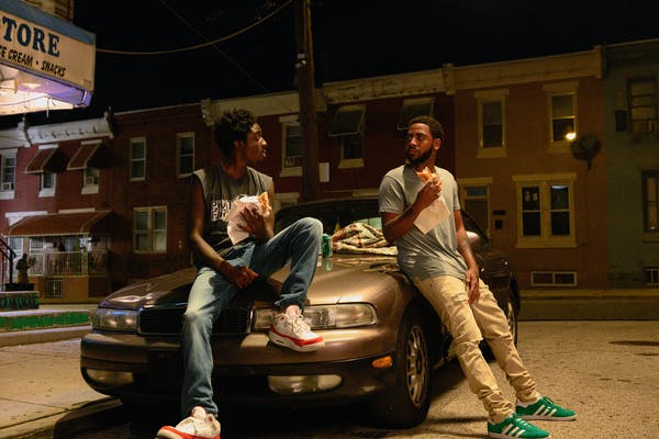 two teens sitting on the front of a car