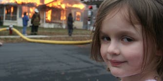 girl standing in front of a house on fire
