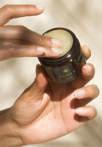 Women dips her fingers into Foria's CBD salve balm with kava.