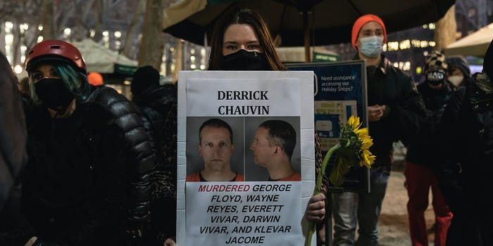 A woman holding a wanted sign for Derek Chauvin.