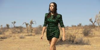 woman in green dress walking in desert