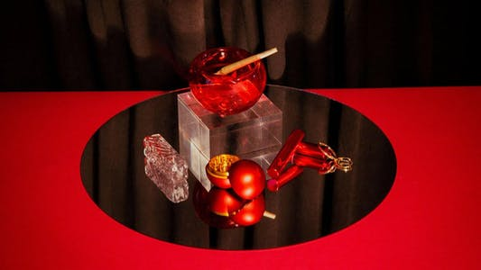 Playboy's retro-inspired smoking accessories on a mirror and red table cloth. Features a glass pipe, glass ashtray, joint holder, rolling tray, and grinder.