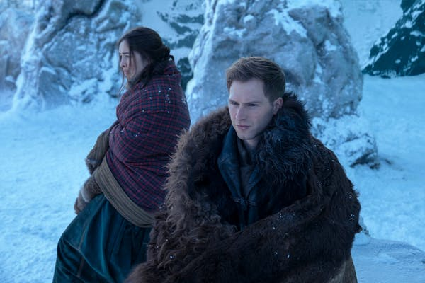 two people huddled in clothes to keep warm