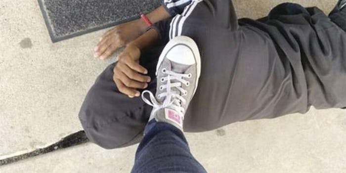 Someone's foot stepping on a black person's neck while they are lying on the ground