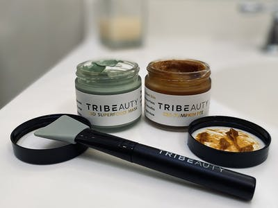 TribeTokes superfood and pumpkin CBD face masks are one of the best stoner gifts for her and him! on the left is a jar of the green superfood mask and on the right is a jar filled with the orange pumpkin mask. in front of it sits a face mask applicator all branded with TRIBETOKES logo.