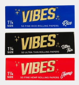 """VIBES Rice Papers in blue packaging, Vibes ultra thin papers in black packaging and VIBES hemp rolling papers in red packaging all feature a gold logo that reads """"VIBES"""""""