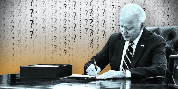 President Joe Biden signing a paper on a desk.