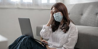 Unhappy woman in mask using laptop while sitting on the floor
