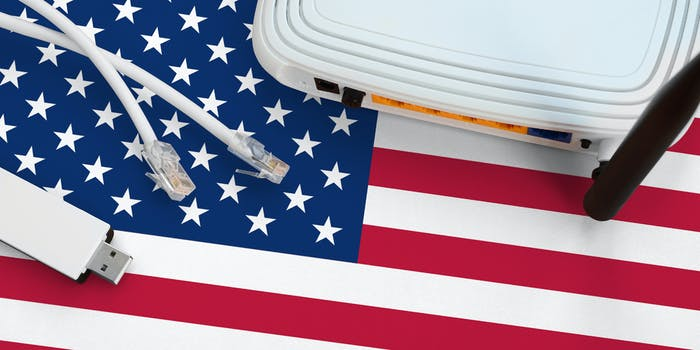 A broadband router, ethernet cables, and USB stick lying on top of an American flag.