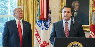 Devin Nunes speaking at a podium at the White House. Former President Donald Trump stands behind him.