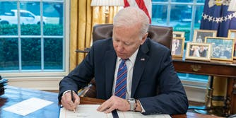 President Joe Biden signing a document in the Oval Office.