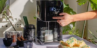 LĒVO II cannabutter machine is busy dispensing infused milk on a table next to the device's accessories, rice krispy treats, and a plant in the background.
