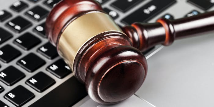 A gavel resting on a laptop's keyboard.