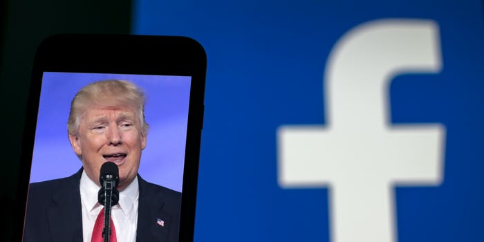 A photo of former President Donald Trump on a phone. In the background, the Facebook logo is blurred out.