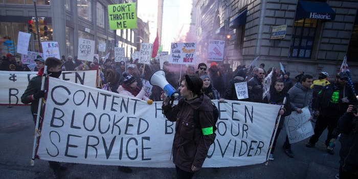 Net neutrality supporters protesting and holding signs that say 'content blocked.'