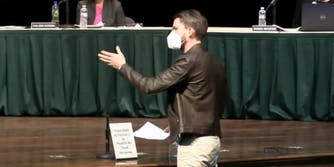 man in leather jacket and mask gestures to people sitting at table on stage