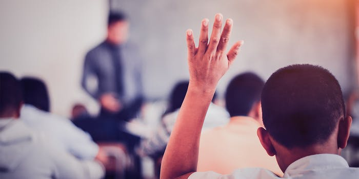 student sitting at their desks and raise their hands in a classroom.