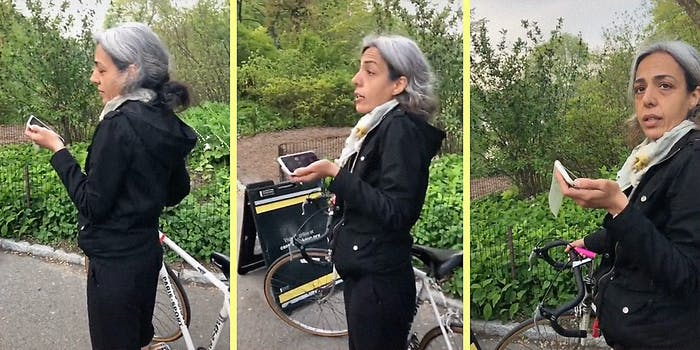 A woman with a phone and bicycle.
